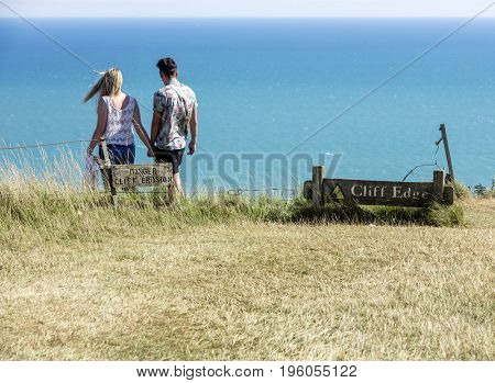 Two unknown people ignore danger signs at known suicide location at Beachy Head cliffs in Sussex, England
