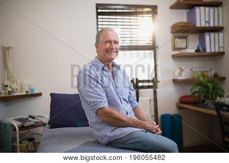 Portrait of smiling senior male patient sitting on bed at hospital ward