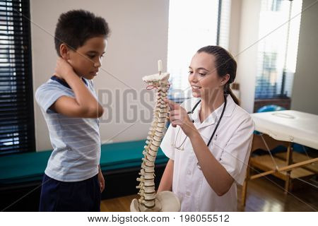 Female therapist pointing at artificial spine while explaining to boy in hospital ward