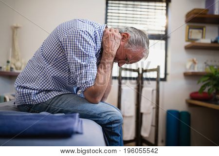 Side view of senior man sitting with neck pain on bed at hospital ward