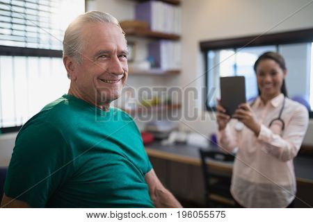 Portrait of smiling senior male patient with female therapist holding digital tablet at hospital ward