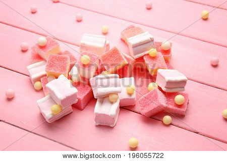 Composition of delicious candies on pink table