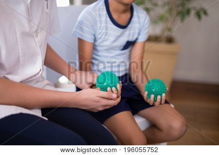 Midsection of female therapist and boy holding stress balls at hospital ward