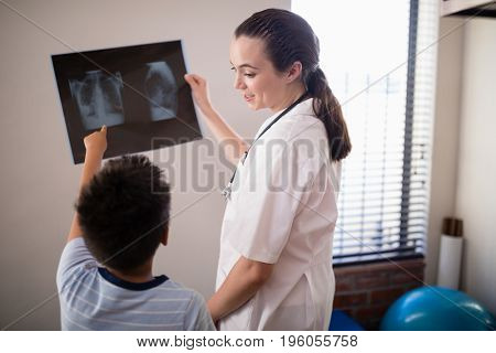 Female therapist looking at boy pointing towards x-ray against wall in hospital ward