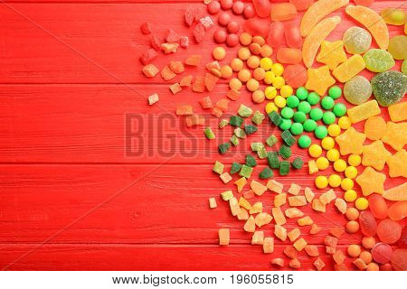 Composition of delicious candies on red wooden background