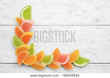 Composition of delicious jelly candies on white wooden table