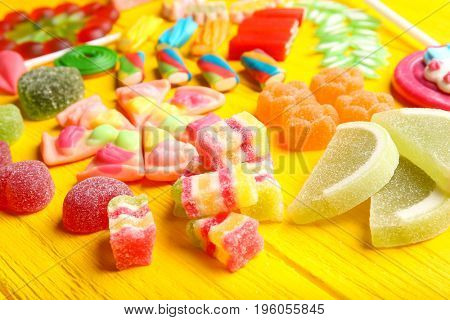 Composition of delicious candies on yellow wooden table