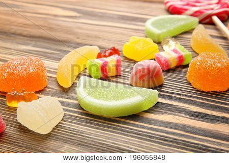Composition of delicious jelly candies on wooden background