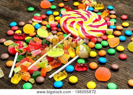 Composition of delicious candies on wooden background
