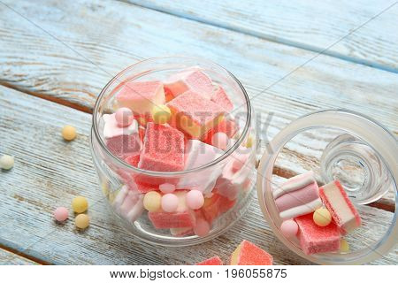 Glass jar with delicious candies on wooden table