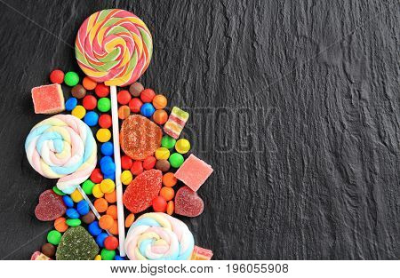 Composition of delicious candies on grey background