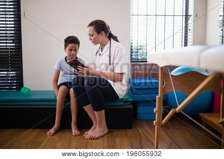 Female doctor showing digital tablet to boy against wall at hospital ward