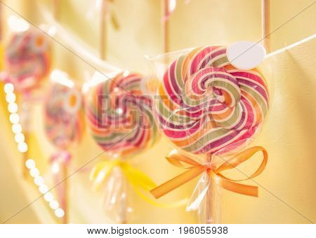 Different lollipops on showcase at candy shop, closeup