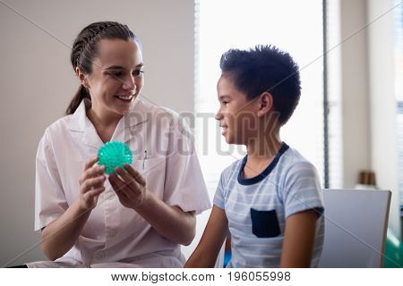 Smiling female therapist showing stress ball to boy at hospital ward