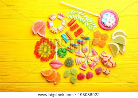 Composition of delicious candies on yellow wooden background