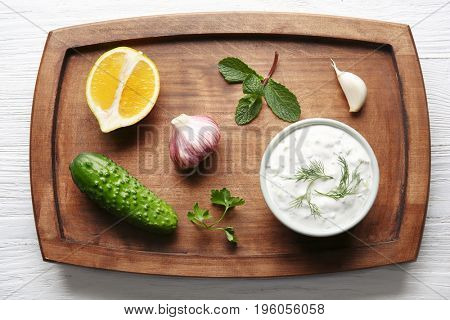 Delicious yogurt sauce in bowl with ingredients on wooden board