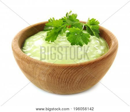 Delicious yogurt sauce with parsley leaves in wooden bowl isolated on white