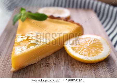 Piece of delicious lemon pie on wooden board, closeup