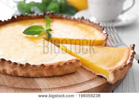Wooden plate with delicious lemon pie on table, closeup