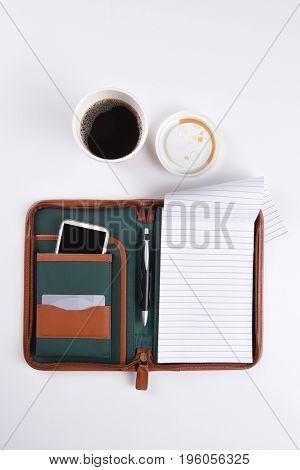 Top view of a paper cup of coffee and a note book on a white desk.