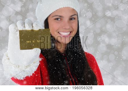 Closeup of a young woman holding a credit card. Focus is on the card woman is not in focus.