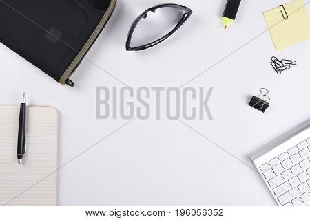 High angle view of a white business desk with pad, pen, keyboard and other accessories, and copy space.
