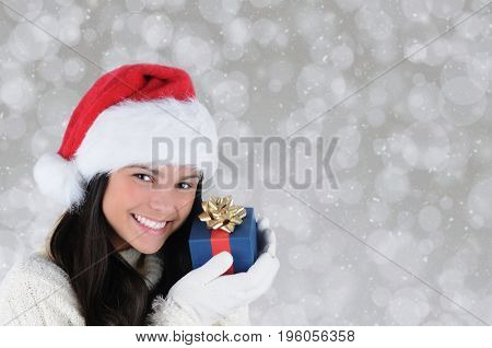 Closeup of a young smiling woman holding a small Christmas present close to her face. Horizontal with copy space.