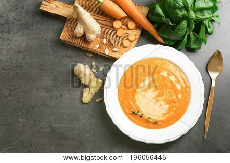 Composition with delicious carrot soup, basil leaves and fresh ginger on table