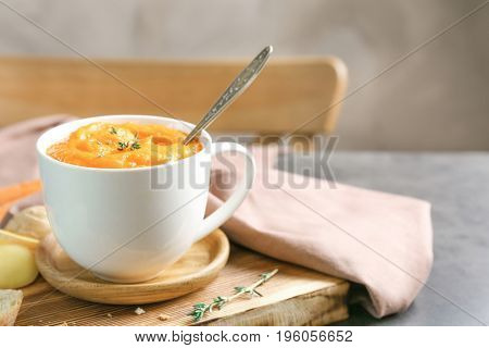 Delicious carrot soup on table