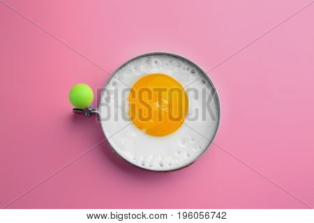 Fried sunny side up egg in round mold on colour background