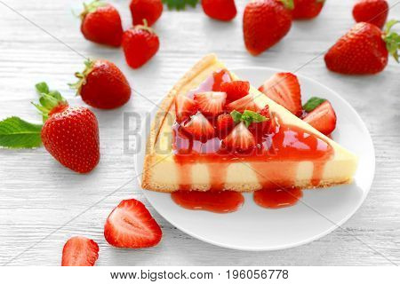 Piece of homemade strawberry cake poured with syrup on plate