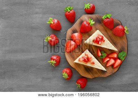 Composition with two pieces of homemade cake with strawberries on table