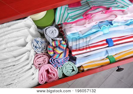 Chest of drawers with clothes and diapers in baby room