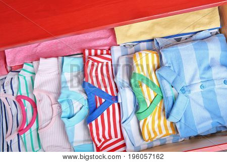 Folded baby clothes in chest of drawers