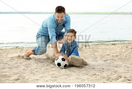 Dad and son playing football together on the beach