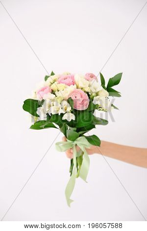 Female hand holding beautiful bouquet with freesia flowers on white background