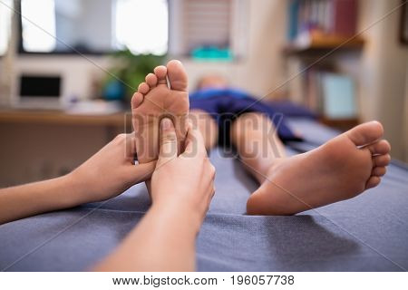 Female therapist massaging sole of foot while boy lying on bed at hospital ward