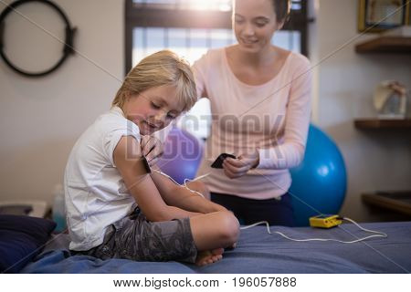 Female therapist positioning electrodes on arm of boy at hospital ward