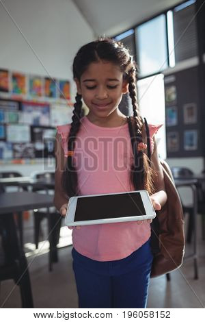 Smiling girl using tablet computer in classroom