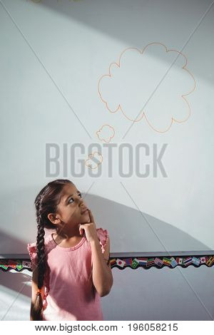 Thoughtful girl looking at speech bubble on whiteboard at school