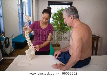 Female therapist explaining shirtless senior male patient with artificial spine at hospital ward