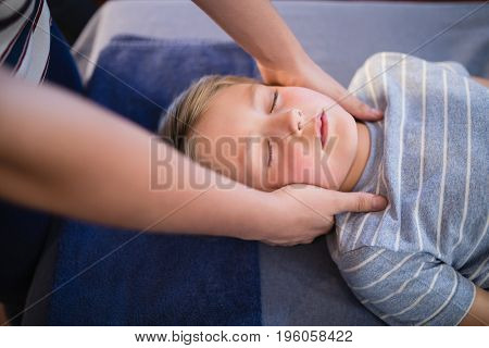 High angle view of female therapist giving neck massage to boy at hospital ward