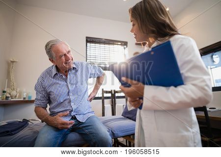 Senior male patient showing back ache to female therapist with file at hospital ward