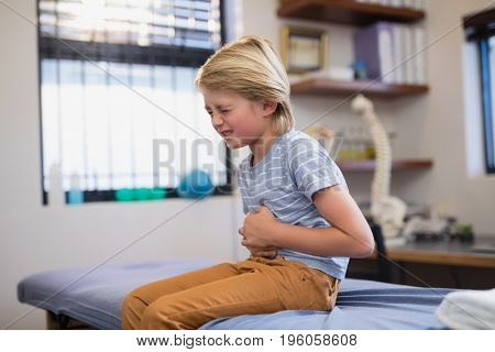 Boy sitting on bed with stomachache at hospital ward