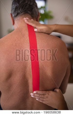 Hands of female therapist applying elastic therapeutic tape on shirtless senior male patient back at hospital ward