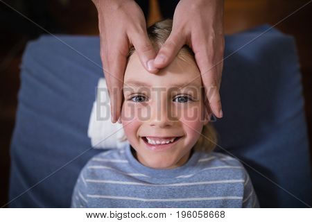 Overhead view of smiling boy receiving head massage from female therapist at hospital ward
