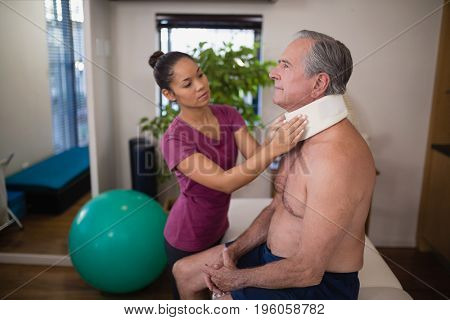 Young female therapist examining neck collar on senior male patient at hospital ward