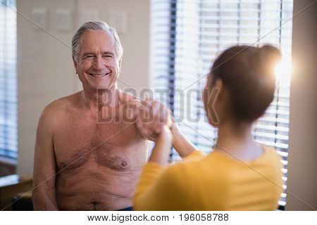Smiling shirtless senior male patient looking at female therapist giving arm massage at hospital ward