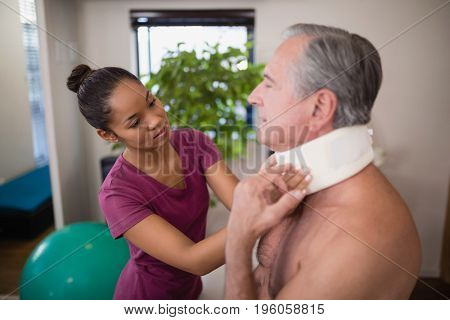 Female therapist examining neck collar of senior male patient at hospital ward