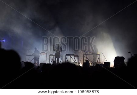 Photo of many people enjoying rock concert, crowd with raised up hands dancing in nightclub, audience applauding to musician band, night entertainment, music festival, happy youth, luxury party